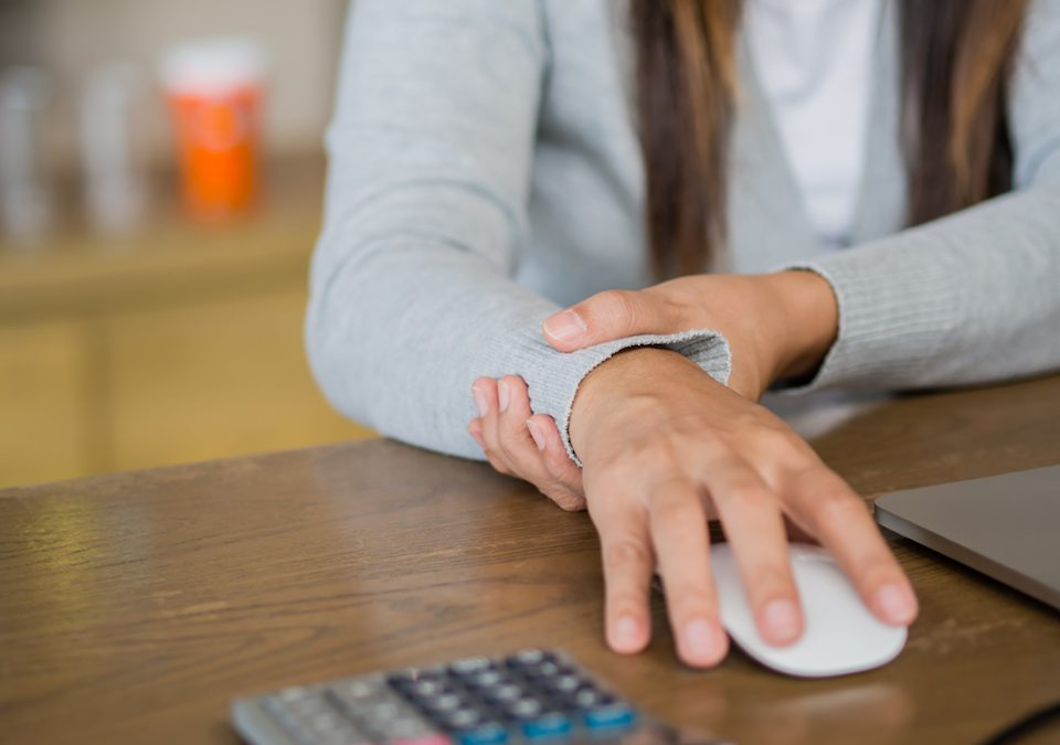 Female entrepreneur with Cumulative Trauma Disorder, wrist pain holding her wrist and her mouse